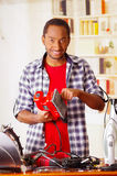 Happy Young African Ecuadorian male Technician fixing a red sander with his screwdriver on office background.  Royalty Free Stock Images