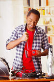 Happy Young African Ecuadorian male Technician fixing a red sander with his screwdriver on office background.  Stock Photo