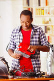 Happy Young African Ecuadorian male Technician fixing a red sander with his screwdriver on office background.  Royalty Free Stock Photos