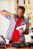 Happy Young African Ecuadorian male Technician repairing an iron with a screwdriver.  Royalty Free Stock Photo