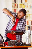 Happy Young African Ecuadorian male Technician repairing a laptop with a screwdriver.  Stock Images