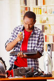 Happy Young African Ecuadorian male Technician repairing a laptop with a screwdriver.  Royalty Free Stock Photo