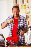 Happy Young African Ecuadorian smiling male Technician repairing a toaster with a screwdriver.  Stock Image