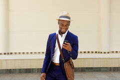 Happy young african guy with bag and mobile phone Royalty Free Stock Images