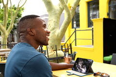 Happy young african man at a cafe with digital tab Royalty Free Stock Photography