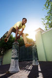 Happy young african man jumping over iron post on sidewalk Stock Images