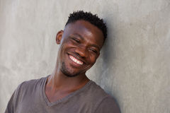 Happy young african man leaning against wall Stock Images
