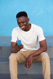 Happy young african man sitting on steps and using phone. Portrait of happy young african man sitting on steps and using smart phone royalty free stock photo