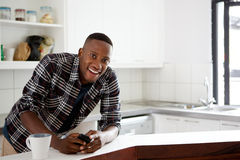 Happy young african man standing in the kitchen Stock Photography