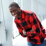 Happy young african man standing outdoors. Portrait of happy young african man standing with his arms crossed and laughing Stock Photography