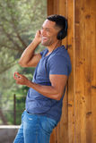 Happy young african man standing outside and listening music. Portrait of happy young african man standing outside and listening music Stock Images