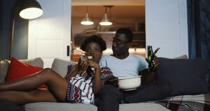 Happy young African positive friends couple watching TV at home on the couch, eating snacks and laughing slow motion.