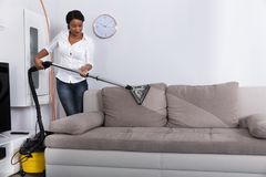 African Woman Cleaning Sofa With Vacuum Cleaner. Happy Young African Woman Cleaning Sofa With Vacuum Cleaner At Home stock photos