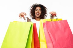 Happy young african woman holding shopping bags. Royalty Free Stock Photos