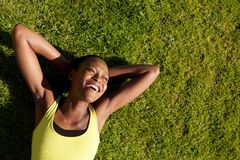 Happy young african woman resting on grass after workout Stock Images