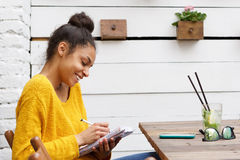 Happy young african woman sitting at cafe and writing notes Royalty Free Stock Images