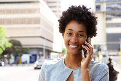 Happy young african woman talking on cellphone Royalty Free Stock Photo