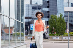 Happy young african woman with travel bag in city Stock Photography