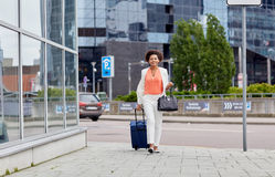 Happy young african woman with travel bag in city Stock Photo