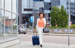 Happy young african woman with travel bag in city Royalty Free Stock Photo