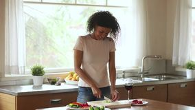 Happy young african woman vegetarian prepare salad meal at home