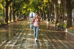 Happy young african woman walking outdoors in park. Photo of happy young african woman walking outdoors in park. Looking aside listening music while chatting by Stock Photo