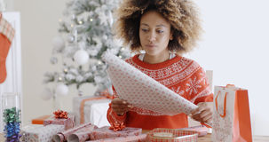 Happy young African woman wrapping presents Stock Photography