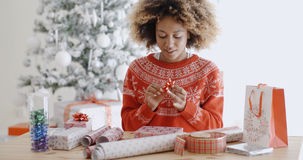 Happy young African woman wrapping presents Royalty Free Stock Photos