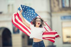 Happy young american school girl holding and waving in the city Stock Photo