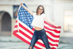 Happy young american school girl holding and waving in the city Royalty Free Stock Photography