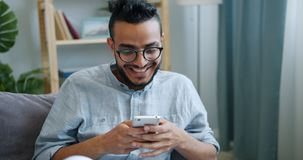 Happy young Arab using smartphone looking at screen with happy face at home. Happy young Arab is using smartphone looking at screen with happy face sitting on stock footage