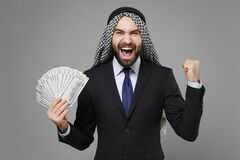 Happy young arabian muslim businessman in keffiyeh kafiya ring igal agal black suit isolated on gray background