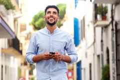 Happy young arabic man laughing with mobile phone and earphones in the city royalty free stock image