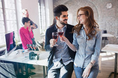 Happy young architects having break and drinking wine Royalty Free Stock Photo