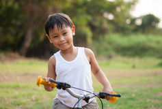 Happy young asia boy riding a bike outdoors Royalty Free Stock Photography