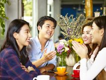 Happy young asian adults chatting in coffee shop Royalty Free Stock Image