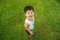 Happy young Asian boy is smiling on a green of garden Royalty Free Stock Photo