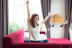 Happy young Asian business woman sitting on red sofa and stretch royalty free stock photos