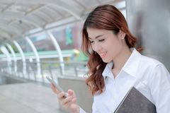Happy young Asian business woman using mobile smart phone at sidewalk of office. Stock Photo