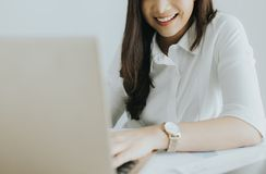 Happy young asian business woman working at her workplace stock image