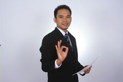Happy young asian businessman with paper and showing ok sign isolated on white. Happy young asian businessman with paper and showing ok sign Royalty Free Stock Image