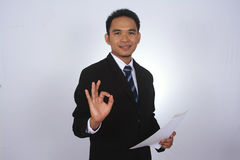 Happy young asian businessman with paper and showing ok sign. Isolated on white Royalty Free Stock Photo