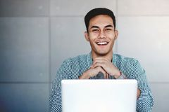 Happy Young Asian Businessman Working on Computer Laptop. In his Workplace. Hands on Chin, Smiling and looking at Camera royalty free stock photography
