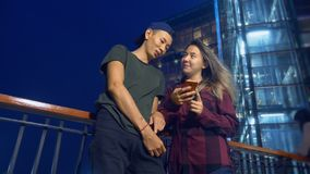 Happy young asian couple boyfriend and girlfriend. use a smartphone while standing on a city street in the evening. stock footage