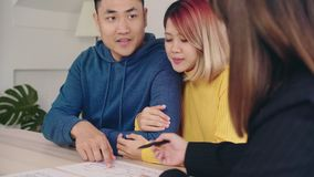 Cheerful young man signing some documents while sitting at desk together with his wife. Buying new house real estate.