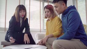 Happy young Asian couple and realtor agent. Cheerful young man signing some documents while sitting at desk together with his wife. Buying new house real stock footage