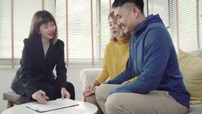 Happy young Asian couple and realtor agent. Cheerful young man signing some documents while sitting at desk together with his wife. Buying new house real stock video