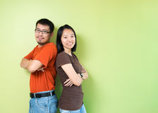 Happy young couple. Happy young Asian couple standing back to back against green wall Stock Photo