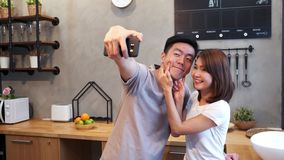Happy young Asian couple using smartphone for selfie while cooking in the kitchen at home. Man and woman preparing healthy food.