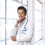 Happy young asian doctor on hospital corridor Royalty Free Stock Image